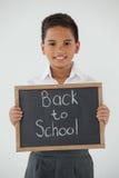Kritiserar hållande handstil för skolpojken med text tillbaka till skolan mot vit bakgrund Arkivfoton
