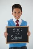 Kritiserar hållande handstil för skolpojken med text tillbaka till skolan mot vit bakgrund Arkivbilder