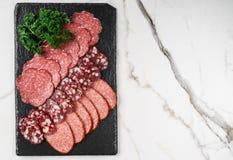 Kritiserar kallt kött för Antipastouppläggningsfatet med prosciuttoen, korven, salami på stenbrädet över marmorerar bakgrund K?tt arkivbild