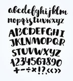 Kritzeln Sie typografische Symbole - übergeben Sie gezogenen Guss über altem gelbem Papier Lizenzfreie Stockfotos