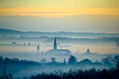 Krizevci cathedral in fog landscape royalty free stock images