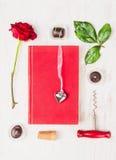 Kärlekshistoria som komponerar med boken, hjärta, den röda rosen, choklad och korkskruvet på vit bakgrund Arkivbild