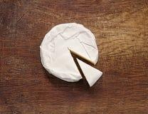 Krämig Brie på lantlig träbakgrund Arkivbild