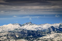 Krn peak under storm clouds, Julian Alps, Slovenia. The peak of Krn Julian Alps, Triglav National Park, Slovenia with rocky terrain of limestone slopes and layer Royalty Free Stock Photo