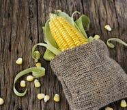 Körner von Mais auf einem Pfeiler und von Sack auf Holztisch Stockfotos