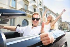 Körning för tummar för bilchaufför lycklig geende upp - av par Royaltyfri Bild