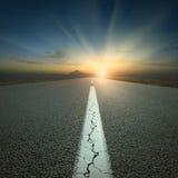 Körning på den öppna vägen in mot berget på soluppgång Arkivfoton