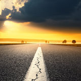 Körning på en tom asfaltväg på soluppgång Royaltyfri Foto