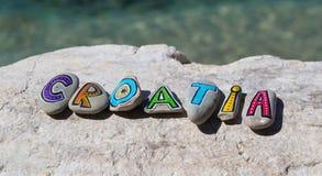 Kroatien-Aufschrift, gemalte Steine auf dem Felsen, adriatisches Meer im Hintergrund Lizenzfreie Stockfotos