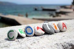 Kroatieninskrift på stenarna med Adriatiskt havet i bakgrunden arkivbild