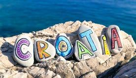 Kroatieninskriften som göras av målade stenar vaggar på, havsbakgrund Royaltyfria Foton