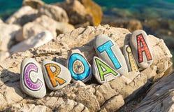 Kroatiennamn som göras av färgrika målade stenar på vagga, havsbakgrund Royaltyfri Foto