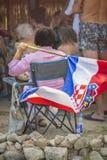 Kroatisches Fußballfan hält eine Staatsflagge stockbild