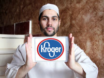 Kroger stores logo. Logo of kroger stores on samsung tablet holded by arab muslim man Stock Photos