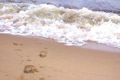 Kroki na piasku na plaży, iść fala obraz stock