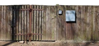 Krokigt fult trälantligt åldrigt staket med brevlådan som isoleras på arkivbilder