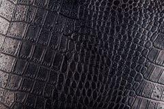 Krokodil of slang de achtergrond van het huidleer Zwarte die textuur met waterdalingen wordt behandeld stock fotografie