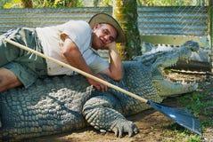 Krokodilbonden Mick Tabone lägger på den största gigantiska reptilen som hålls bak staketet i Australien i den Jonston floden, Au Royaltyfria Bilder