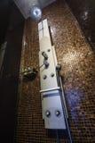 Krom pläterad stänkdusch med sprejare på den belade med tegel väggen Fotografering för Bildbyråer