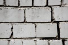 Kromme zwart-witte muur van blokken met een barst stock afbeeldingen
