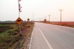 Krommeweg op platteland met verkeersteken twee in Thailand stock afbeeldingen