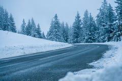 Kromming in een ijzige sneeuwweg door de winterbossen Royalty-vrije Stock Foto