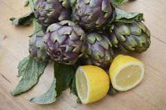 Kronärtskockor och citroner på trä Arkivbild