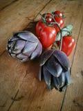 Kronärtskockor och tomater Arkivbild