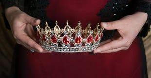 Krona med röda gemstones i händer Lyckat royaltyfri foto