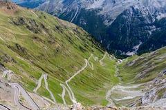 Kronkelige die bergweg door groene heuvels wordt omringd Royalty-vrije Stock Foto's