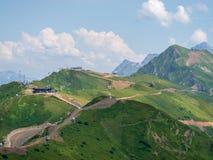 Kronkelige weg tot de bovenkant van een hoge bergketen met kabelwagens Krasnaya Polyana, Sotchi, de Kaukasus, Rusland royalty-vrije stock foto's