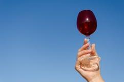 Kronkelt het rode wijnglas van de handgreep zich stam op blauwe hemel Stock Fotografie