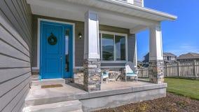 Kroon op blauwe deur van huis met portiek en treden stock afbeeldingen