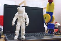Kropivnitskiy, Ukraina – 12 mogą, 2018: 3D drukował astronauty, kosmonauty, robota na tle przyrząda i laptopu, kosmita obraz royalty free