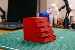 Kropivnitskiy, Ukraina – 12 mogą, 2018: 3D drukował czerwonego plastikowego dresser na tle laptop i przyrząda Meble model zdjęcie royalty free