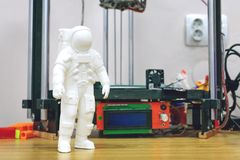 Kropivnitskiy, Ukraine – 12 may, 2018: 3D printed astronaut, cosmonaut on the background of three dimensional 3d printer. Spaceman model stock photography