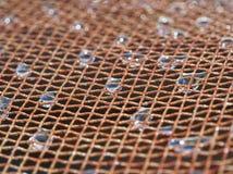 Krople woda na kruszcowej sieci Obraz Stock