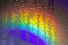 Krople woda na szkle z odbiciem tęcza, zdjęcie stock
