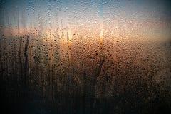 Krople woda na zaparowywającym okno Na zewnątrz okno piękny zmierzch fotografia stock