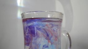 Kropli farba opuszcza w szkło woda Farba miesza pięknie z wodą Żywo maluje jasną wodę zbiory