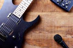 Kropp och fretboard av den moderna elektriska gitarren, den mång- effektprocessorn och mikrofonen på lantlig träbakgrund royaltyfria foton
