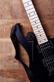 Kropp och fretboard av den moderna elektriska gitarren och mikrofonen på lantlig träbakgrund royaltyfri bild