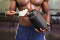 Kroppbyggmästare som rymmer en skopa av proteinblandningen i idrottshall royaltyfri foto
