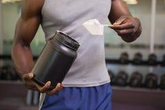 Kroppbyggmästare som rymmer en skopa av proteinblandningen i idrottshall arkivfoton