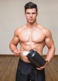 Kroppbyggmästare som rymmer en skopa av proteinblandningen i idrottshall arkivbilder