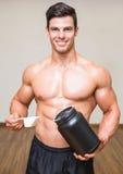 Kroppbyggmästare som rymmer en skopa av proteinblandningen i idrottshall royaltyfria bilder