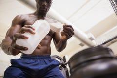Kroppbyggmästare som upp kammar hem proteinpulver royaltyfri foto