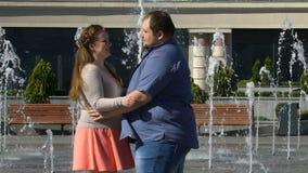 Kropppositivity, romantiskt sjukligt fett par som har roligt och kramar, datum i stad lager videofilmer