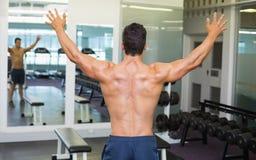 Kroppsbyggare med armar som är utsträckta i idrottshall Royaltyfri Foto