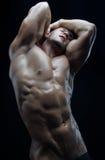 Kroppsbyggare- och remsatema: härligt med den pumpade nakna mannen för muskler som poserar i studion på en mörk bakgrund arkivbild